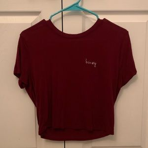 A cropped maroon Honey shirt